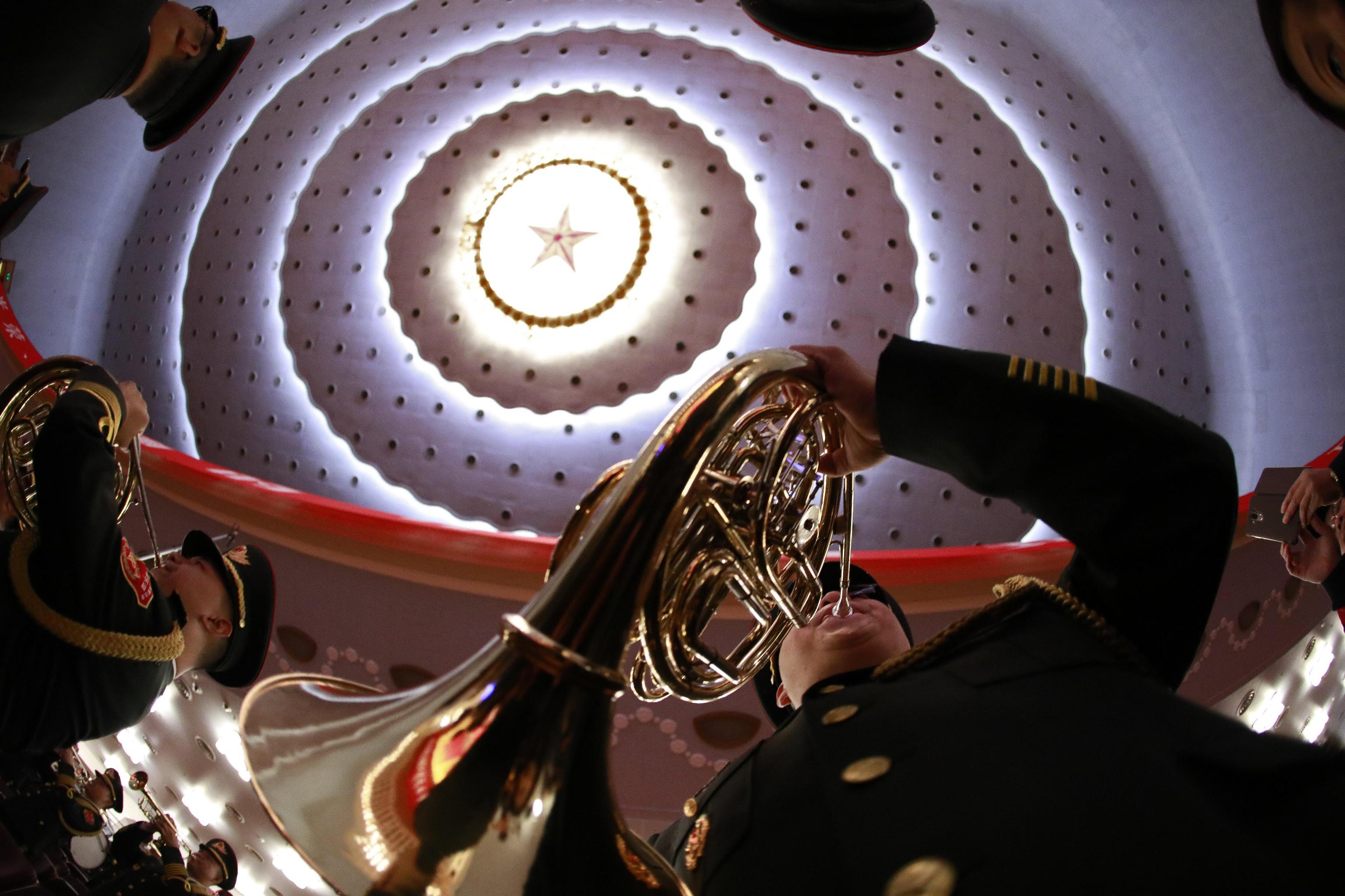I componenti della banda militare provano prima dell'inizio della cerimonia di apertura, sul soffitto domina la stella rossa comunista