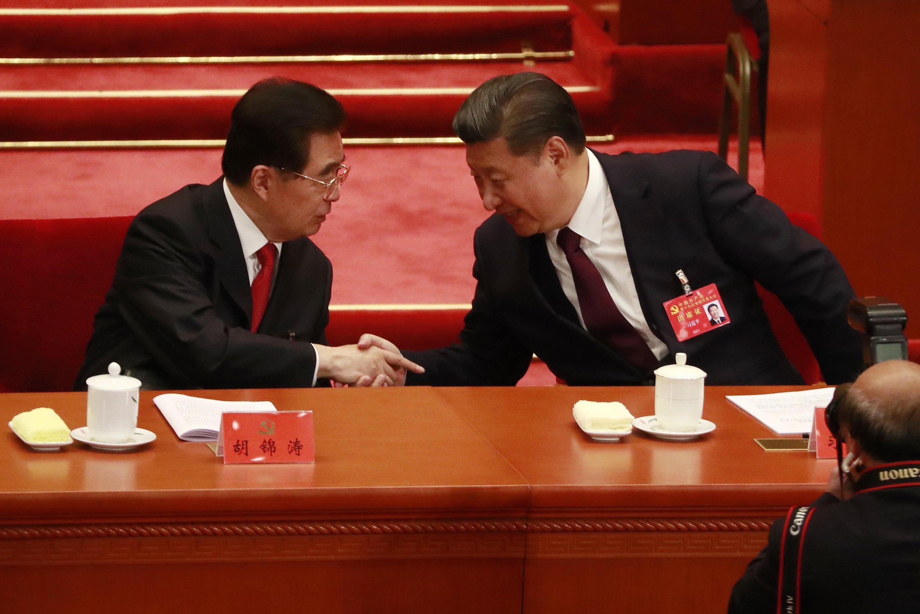 Il Presidente Xi Jinping stringe la mano al suo predecessore Hu Jintao al termine del suo discorso