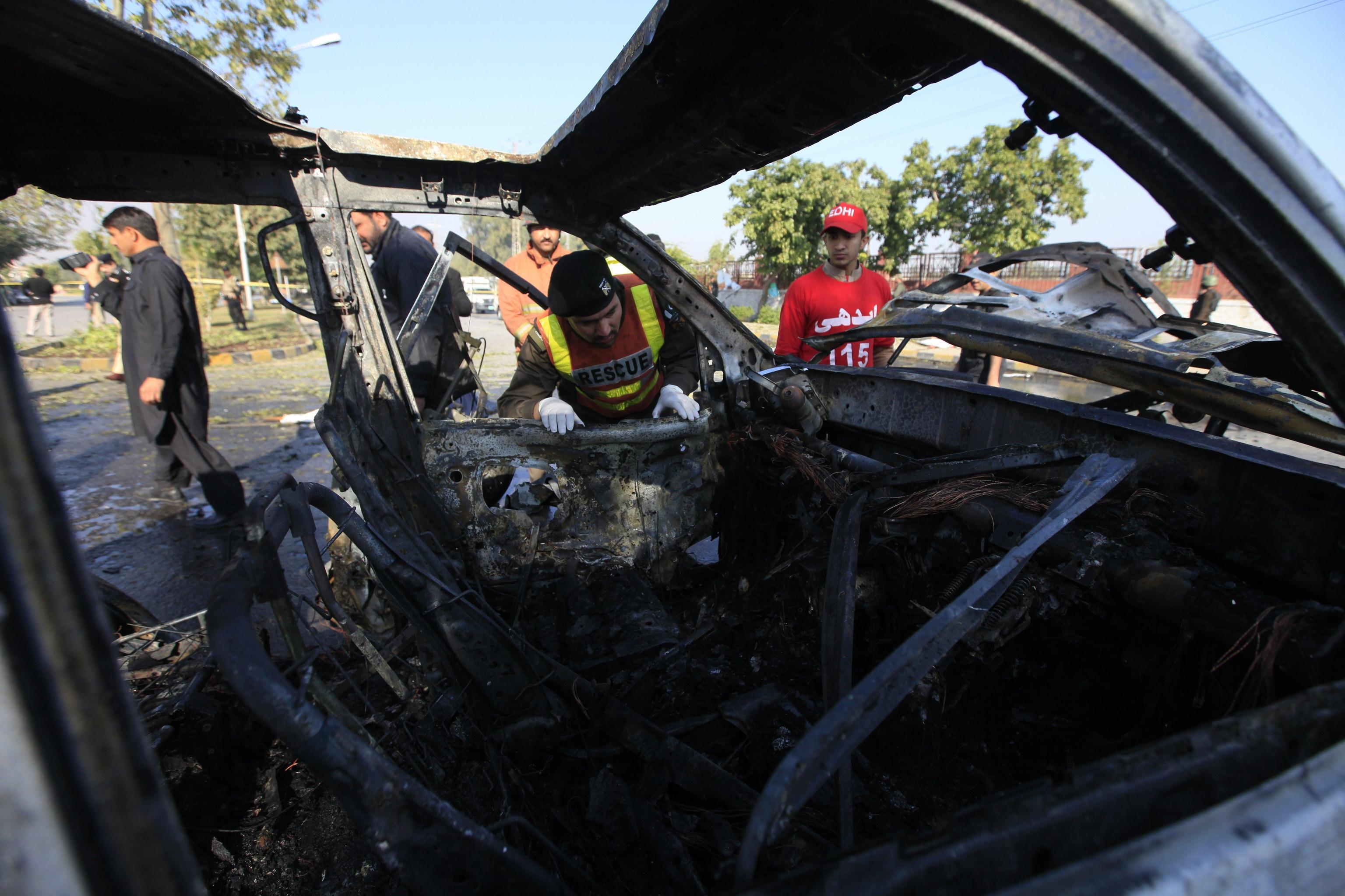 Ufficiali pakistani di pubblica sicurezza ispezionano la scena dell'attentato