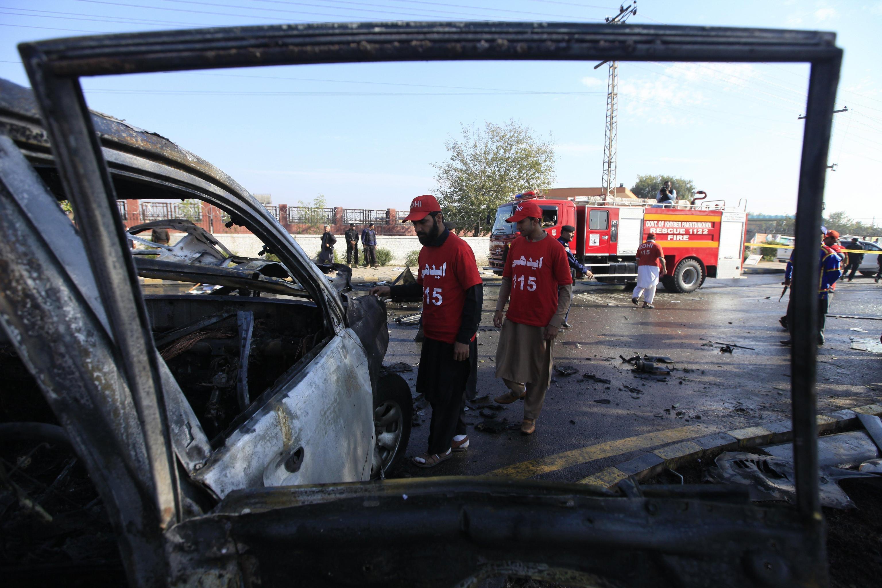 Gli ufficiali di sicurezza pakistani ispezionano i resti del veicolo sul quale viaggiavano l'agente di polizia e i suoi aiutanti