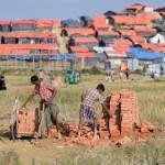 Degli uomini impegnati nel trasporto di mattoni