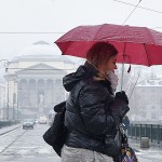 Passante cerca di proteggersi dalla neve con un ombrello