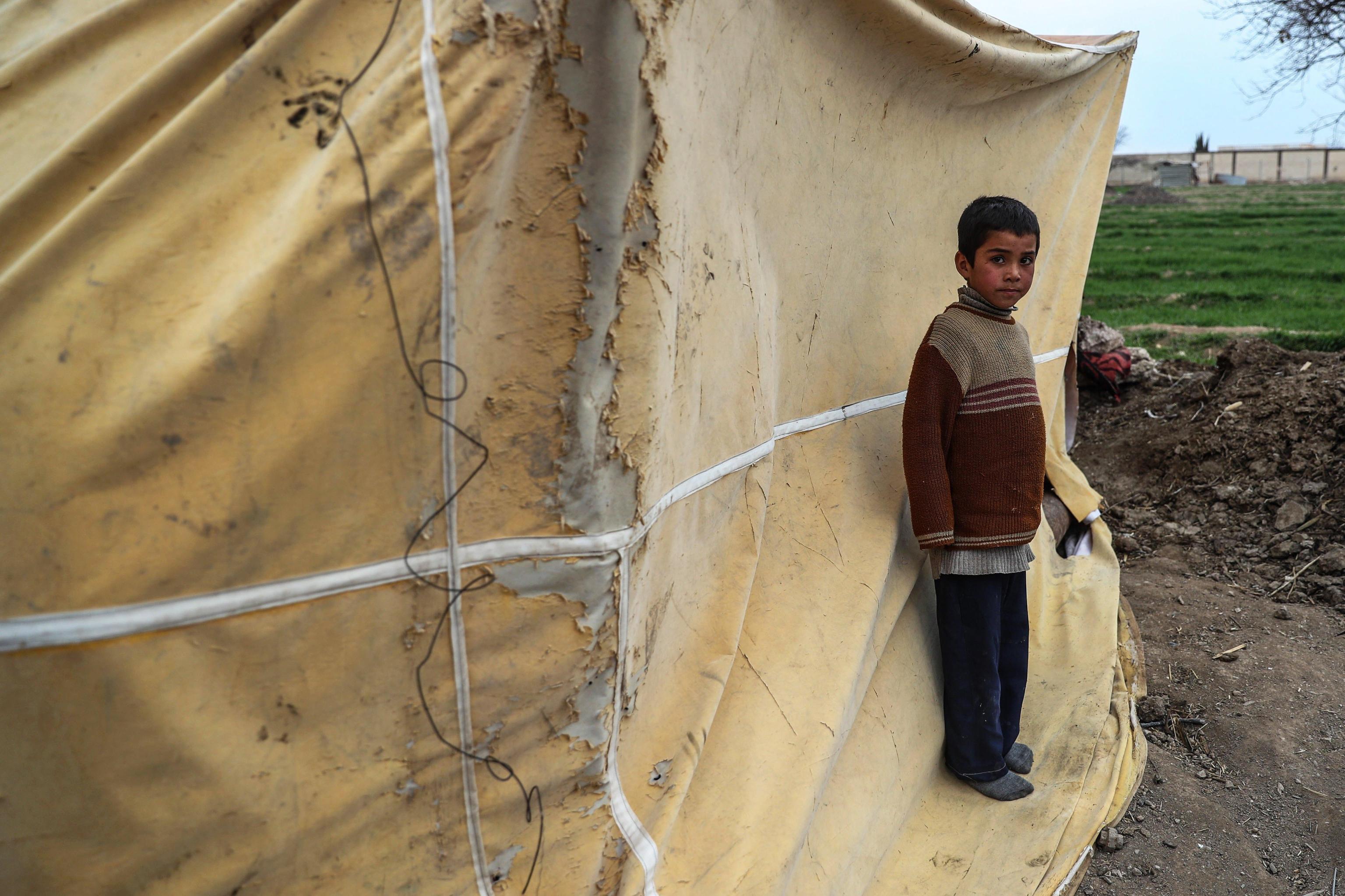 Un bambino sta fuori dalla tenda usata come cucina nel suo rifugio ad al-Ashari