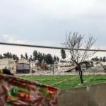 Uno sfollato siriano stende i panni. Alle sue spalle quello che rimane di al-Asha'ari city