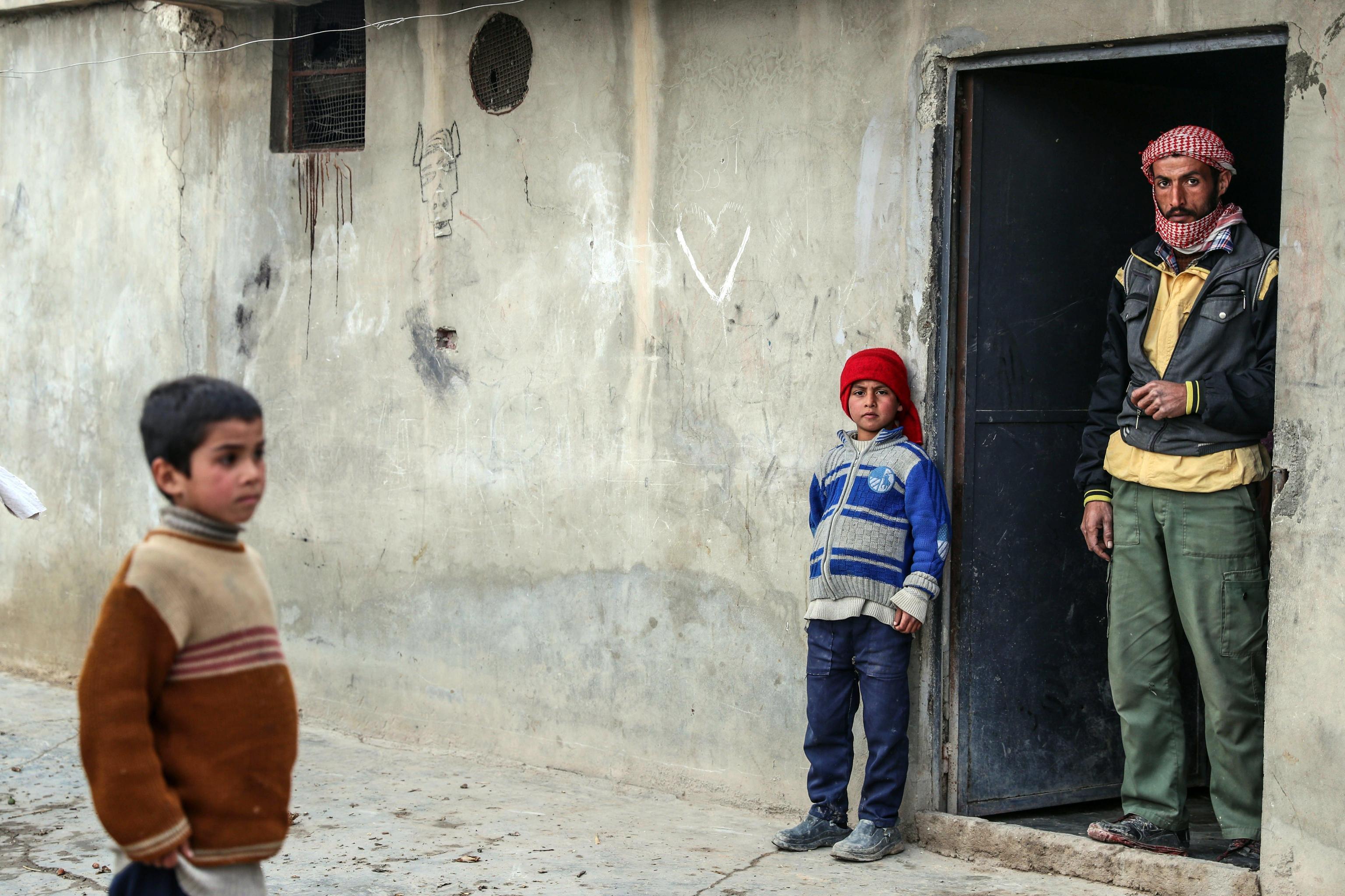 Padre e figli, davanti al loro rifugio ad al-Asha'ari