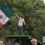 Un manifestante sventola la bandiera messicana