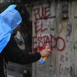 """Un manifestante scrive su un muro """"E' stato lo Stato"""", in relazione alla scomparsa degli studenti"""