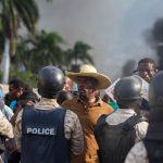 Un uomo discute con degli agenti di polizia durante la protesta