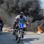 Alcuni motociclisti passano attraverso le barricate infuocate durante le proteste