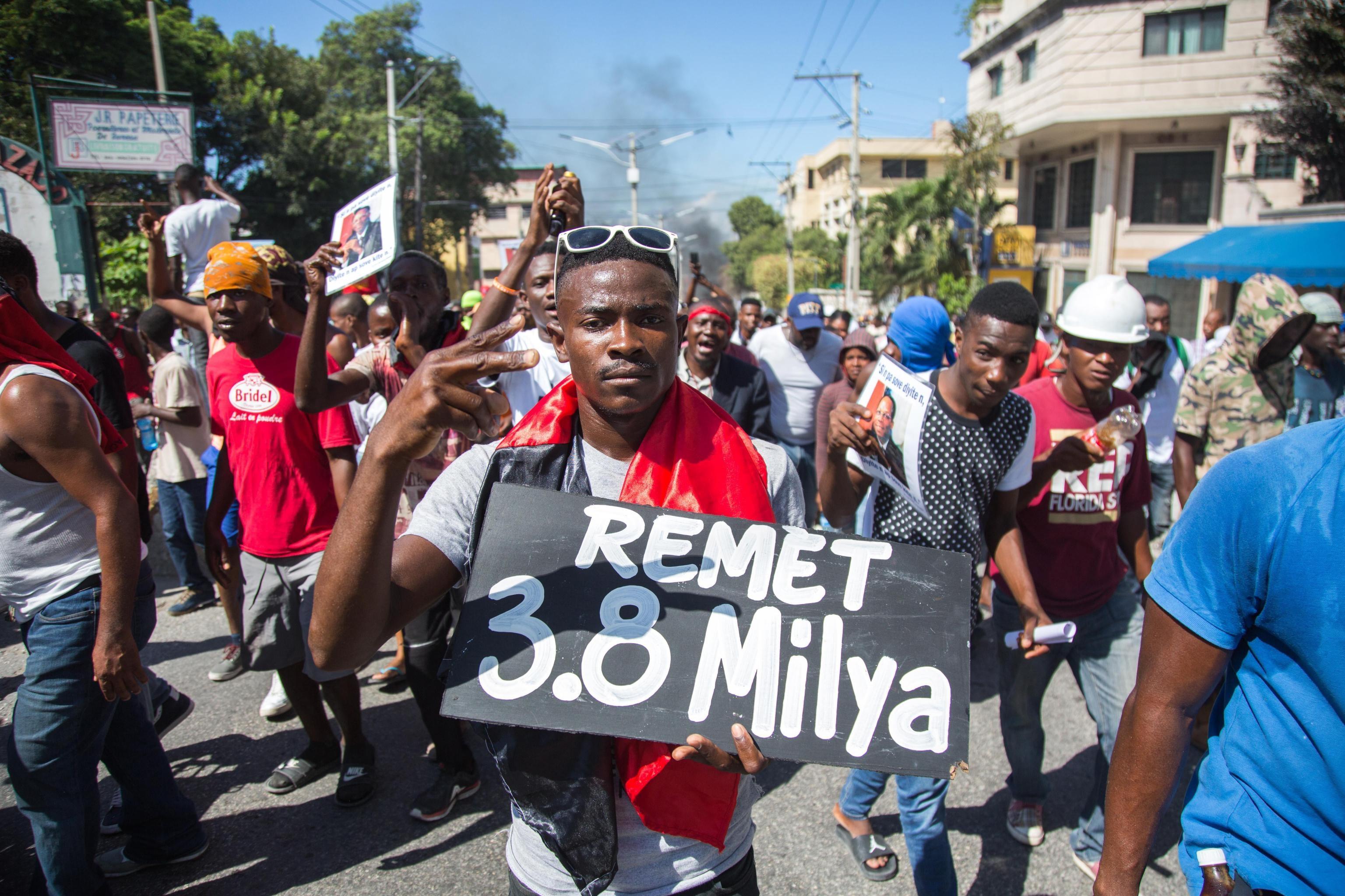 Un uomo con un cartello di protesta che cita i 3,8 miliardi di dollari ricevuti dal governo