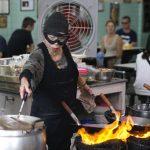 La chef e proprietaria del Raan Jay Fai, Supinya Chansuta, mentre cucina con la sua mascherina