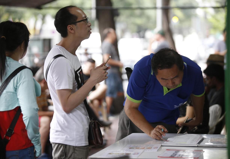 I clienti scrivono il loro nome su un'apposita lista per prenotare un posto al Raan Jay Fai