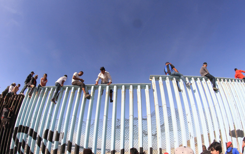 I migranti oltrepassano il recinto che divide i due Paesi