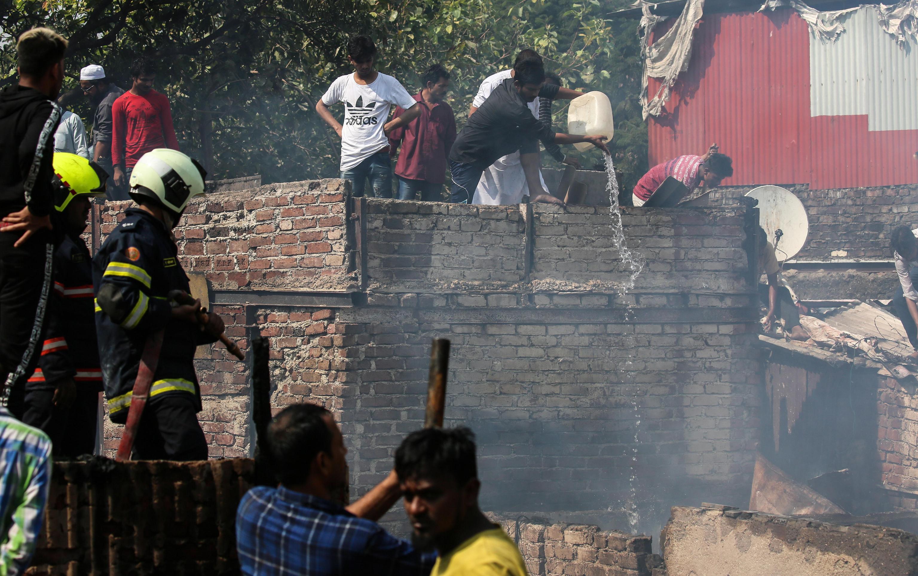 Gli abitanti delle capanne aiutano i vigili del fuoco locali a spegnere l'incendio che ha distrutto la baraccopoli