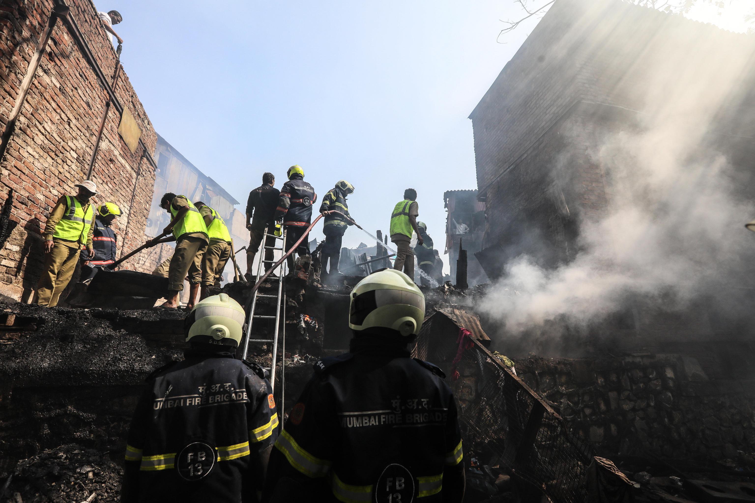 Gli abitanti delle capanne distrutte dall'incendio osservano i vigili del fuoco che continuano a lavorare