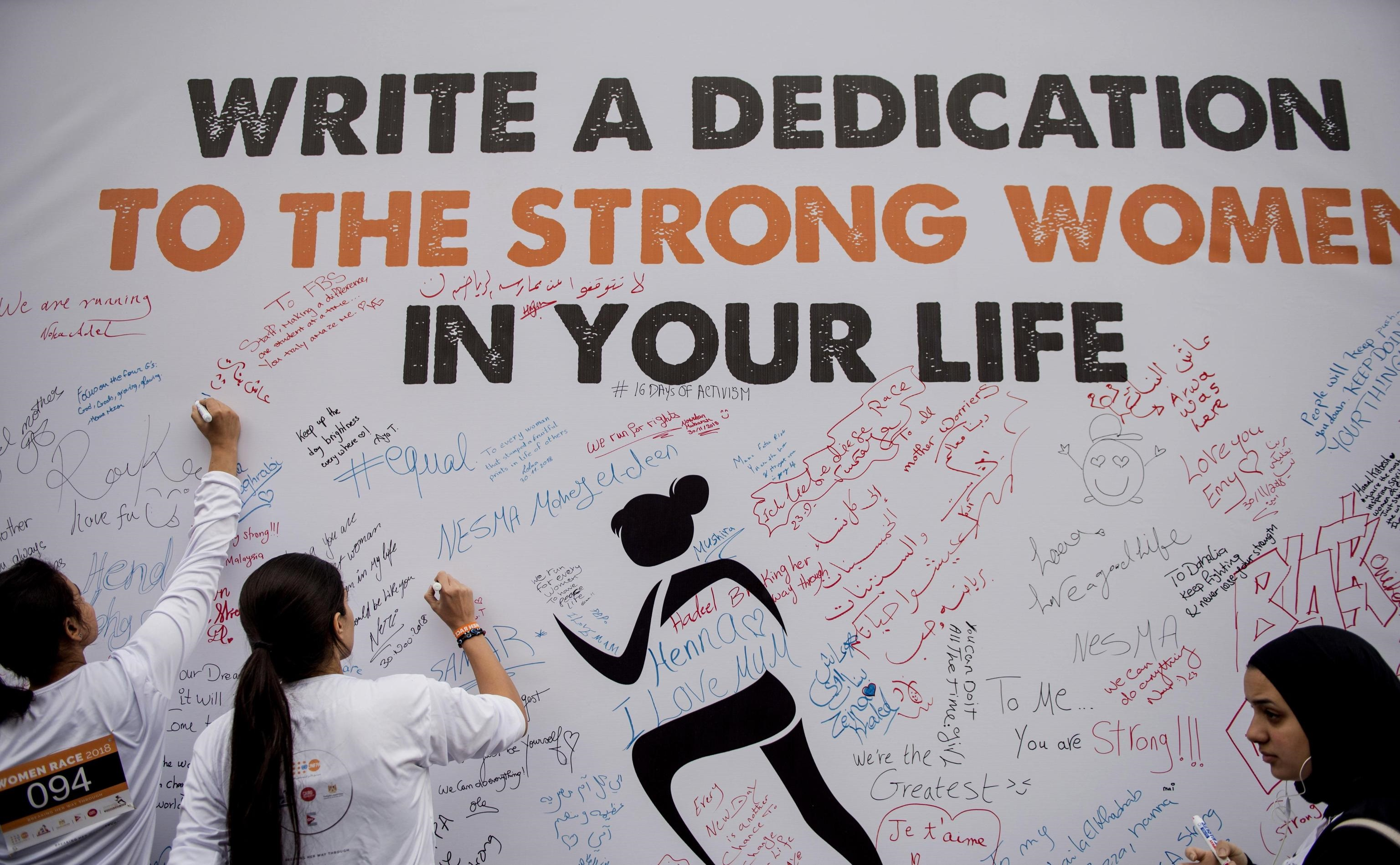 Due ragazze scrivono frasi di incoraggiamento per tutti coloro che parteciperanno alla corsa