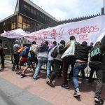Un gruppo di operatori portuali a chiamata tenta di abbattere il cancello del porto di Valparaiso