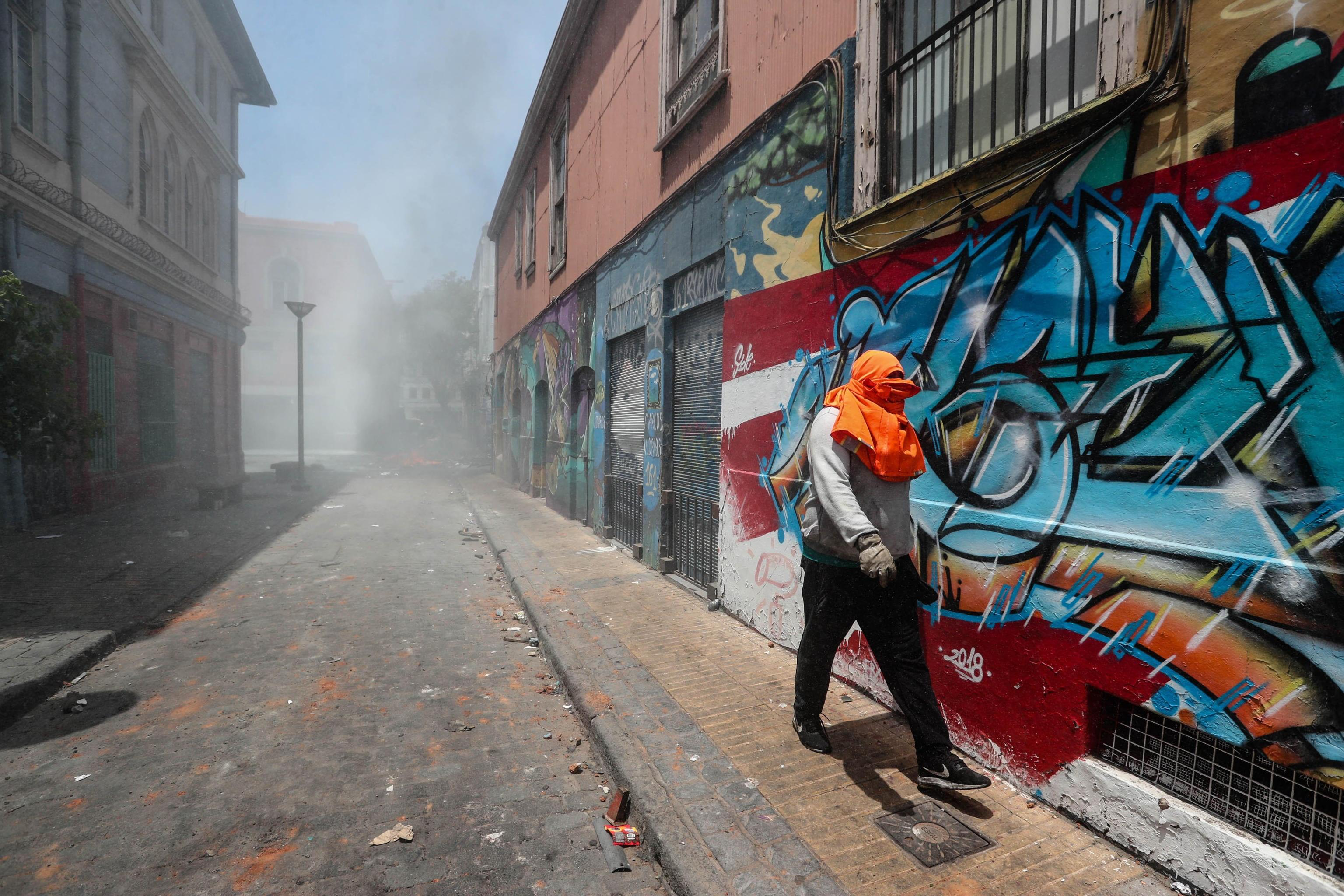 I gas lacrimogeni lanciati dalla polizia non frenano gli operai portuali, per l'occasione mascherati