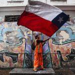 Un manifestante sventola la bandiera cilena davanti al sindacato degli operatori portuali