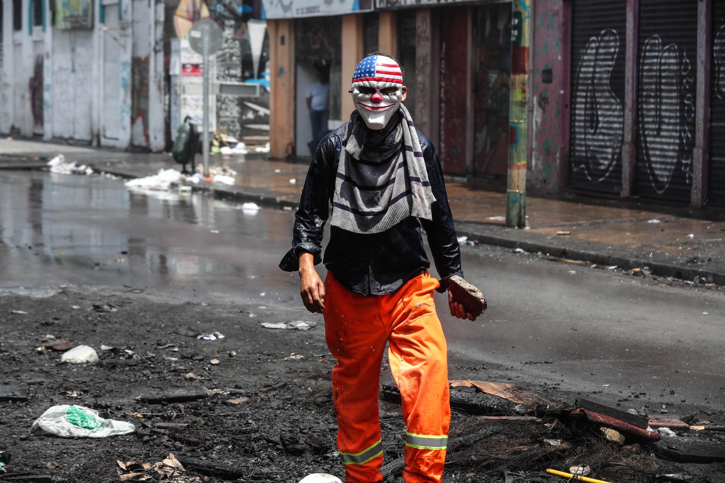 Operaio portuale con una maschera caricaturale degli Usa, in protesta contro il governo a Valparaíso, in Cile