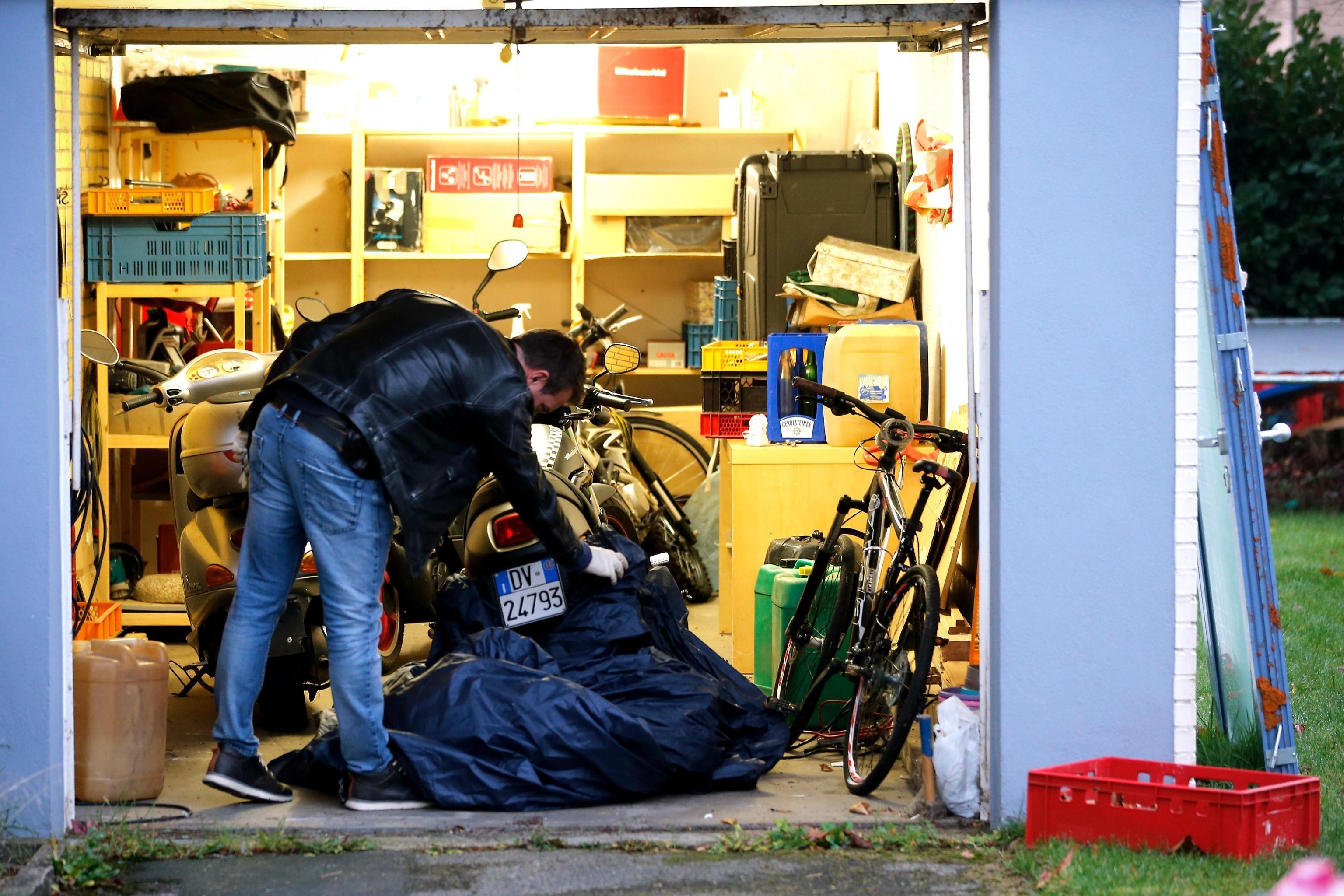 Un poliziotto svolge la perquisizione all'interno di un garage