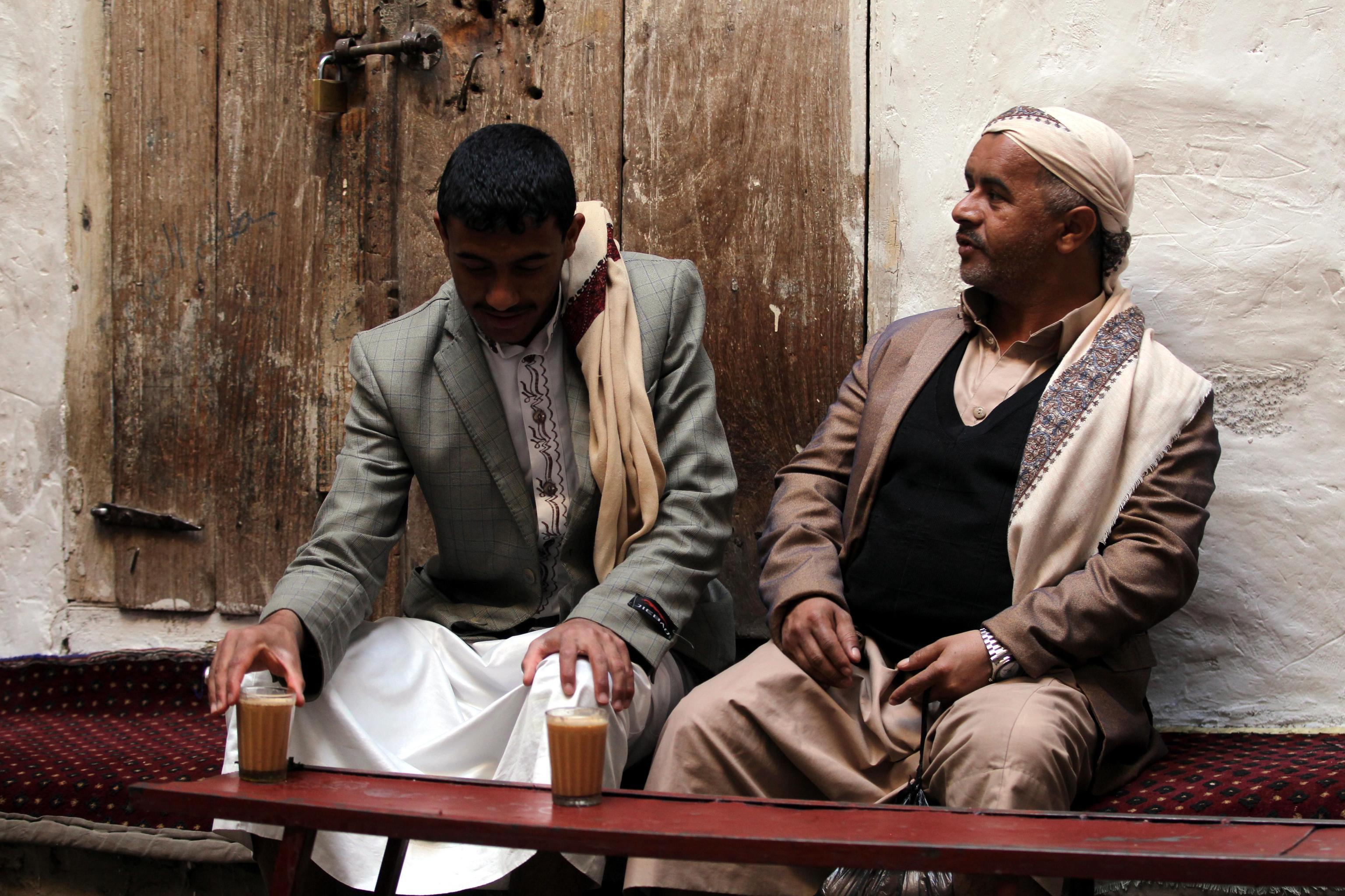 Nei loro vestiti ricercati, due signori scambiano battute mentre sorseggiano un caffè.