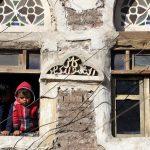 Due bambini sono affacciati ad una finestra, guardando la folla passare.