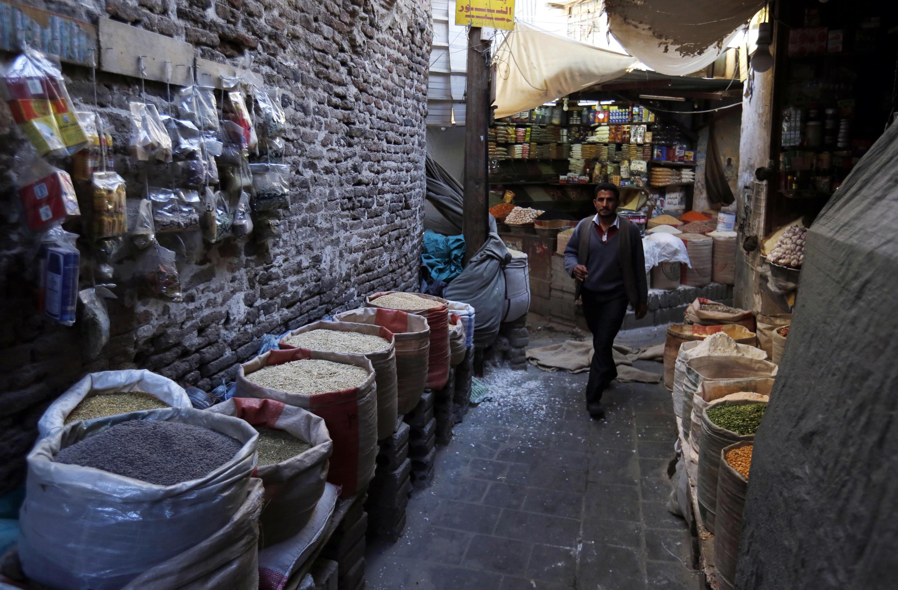 Uno yemenita passeggia lungo le vie anguste del mercato, ricco di prodotti e spezie.