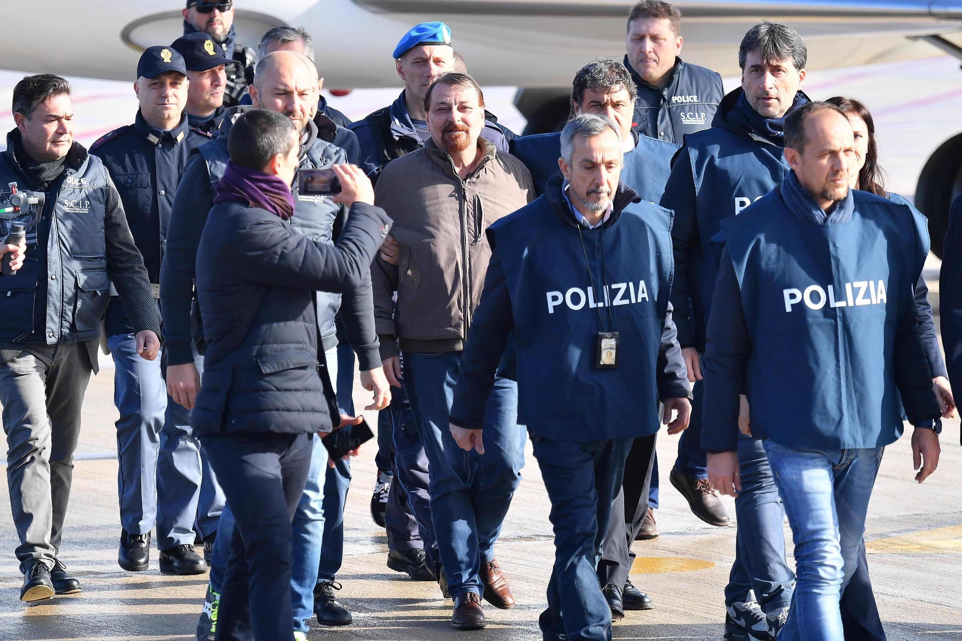 Cesare Battisti, appena sbarcato in Italia, viene scortato dalla Polizia italiana.