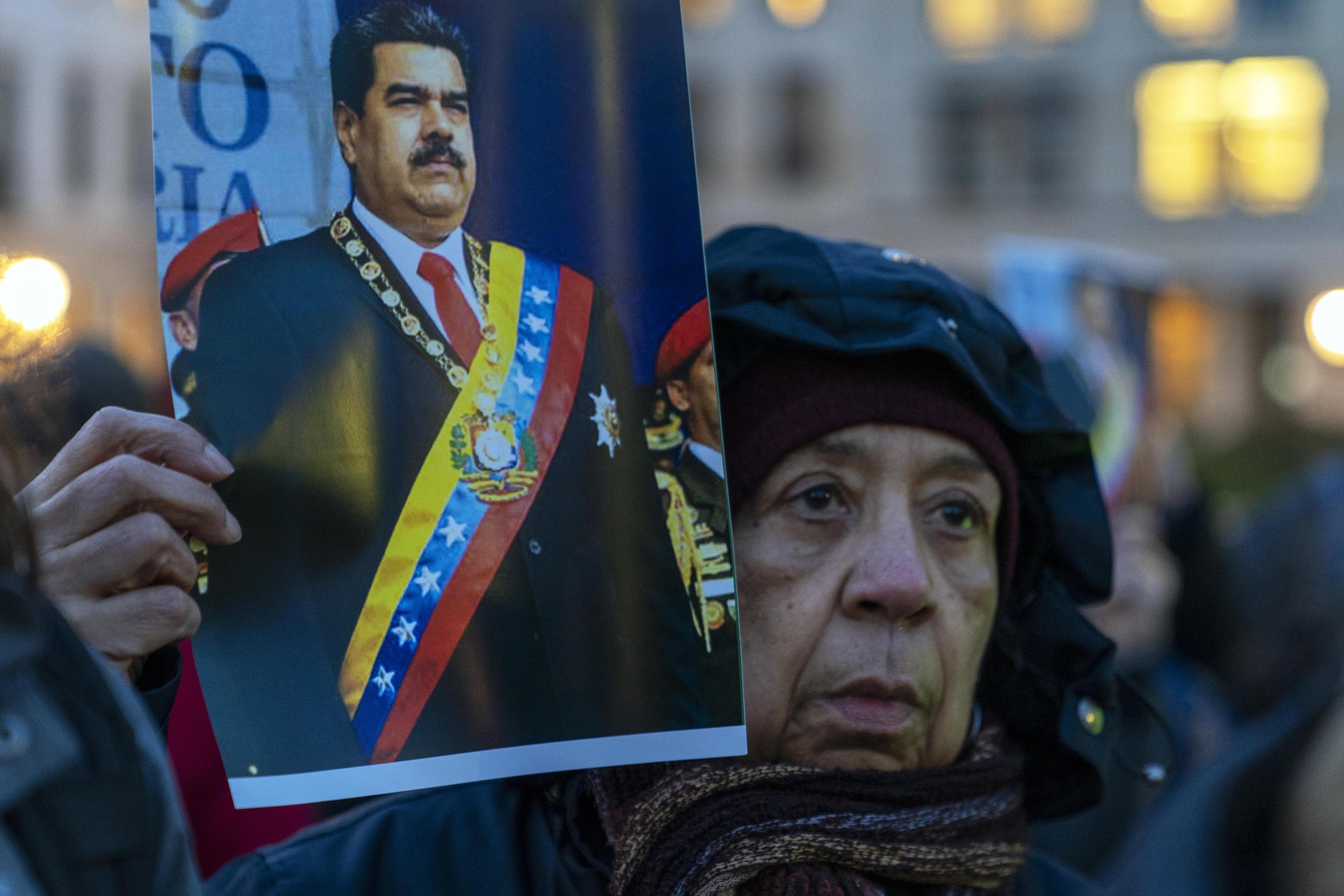 Una donna a Berlino tiene il ritratto di Nicolas Maduro