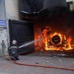 Un vigile del fuoco tenta di spegnere un veicolo dato in fiamme dai manifestanti