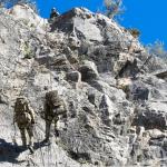 I soldati marciano verso la parete rocciosa