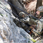 I militari usano funi per scalare la parete rocciosa