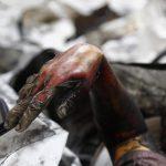La mano di una vittima dell'incendio che esce fuori dalle macerie
