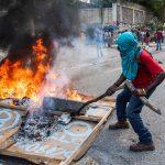 Un manifestante a volto coperto incendia pneumatici e insegne in protesta contro il presidente Moise