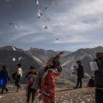 Una ragazza tibetana getta in aria un foglio con preghiere e speranze vicino al monastero di Labrang