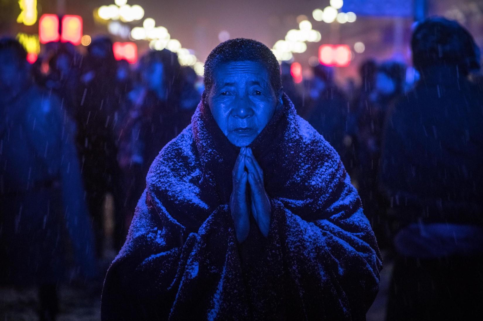 Una suora buddista prega durante una cerimonia con sculture fatte di burro di yak nel monastero di Labrang