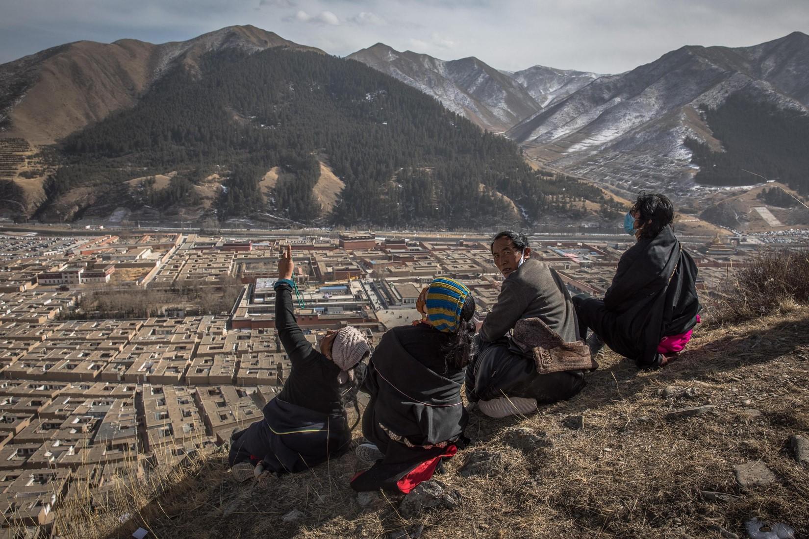 Un gruppo di tibetani seduti sulla stessa collina che domina il monastero di Labrang