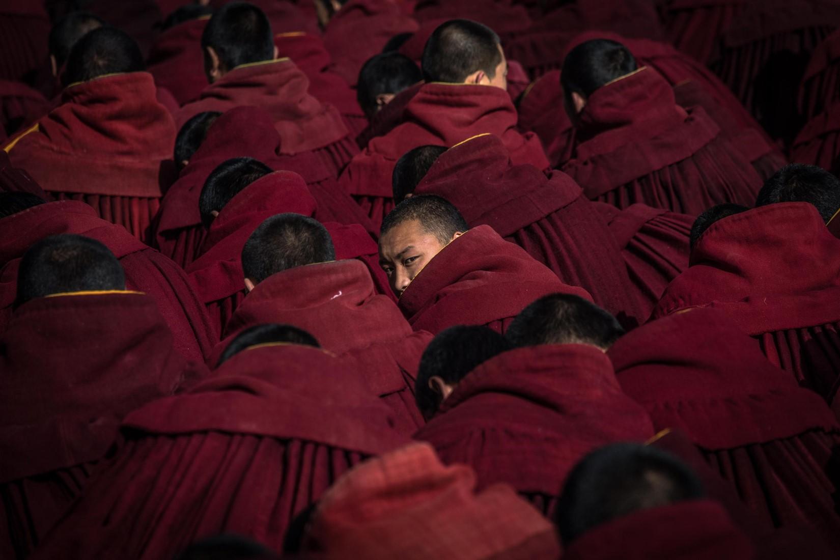 Dettaglio dei monaci buddisti, nei loro abiti tradizionali, mentre aspettano di pregare
