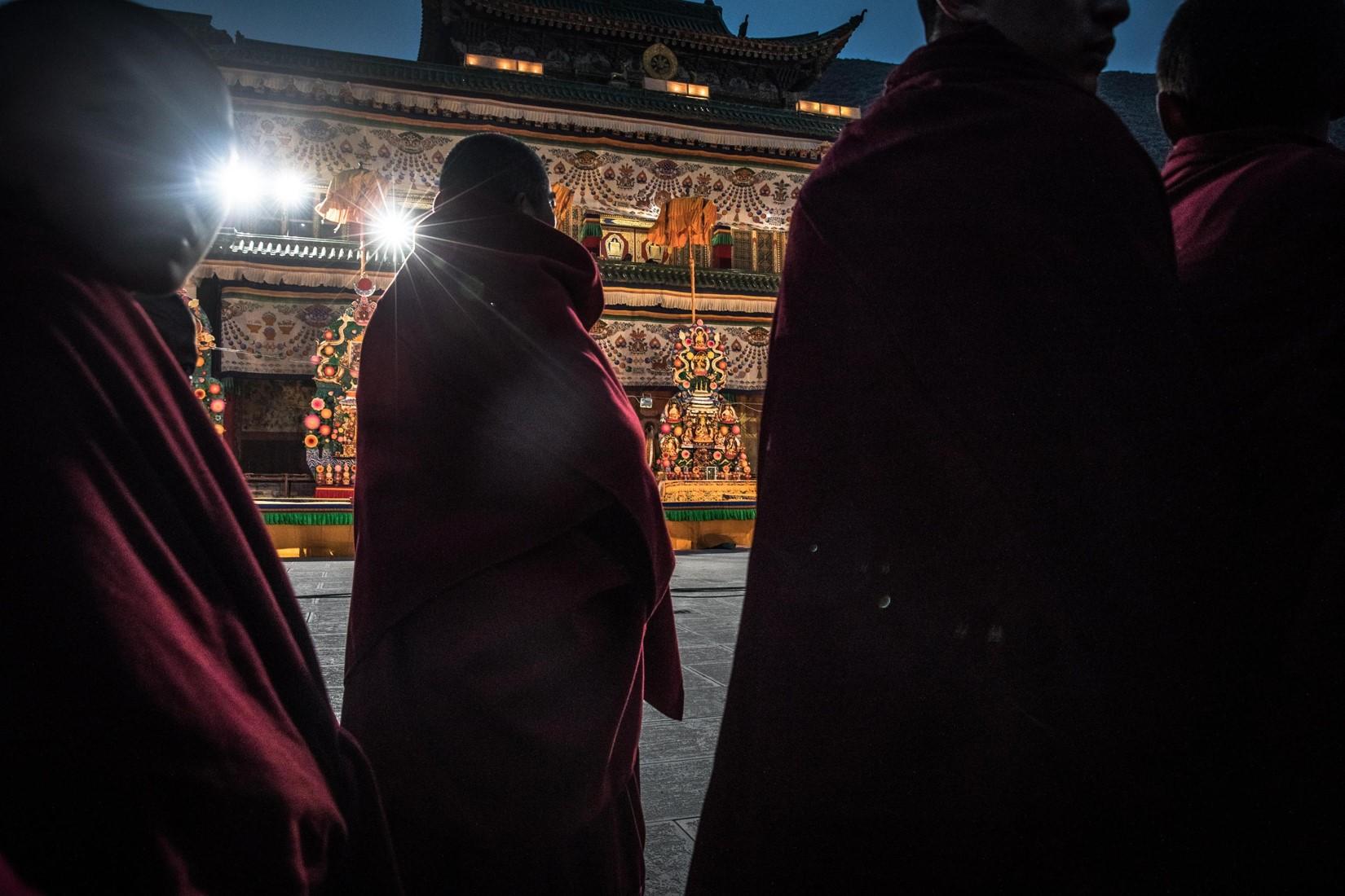 Alcuni monaci buddisti tibetani assistono alla cerimonia con le sculture fatte di burro di yak