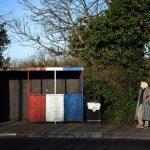 Una donna aspetta l'autobus ad una fermata dipinta con i colori degli unionisti vicino al confine