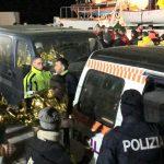 I migranti scendono ordinatamente dalla nave. Il primo di loro è un minore