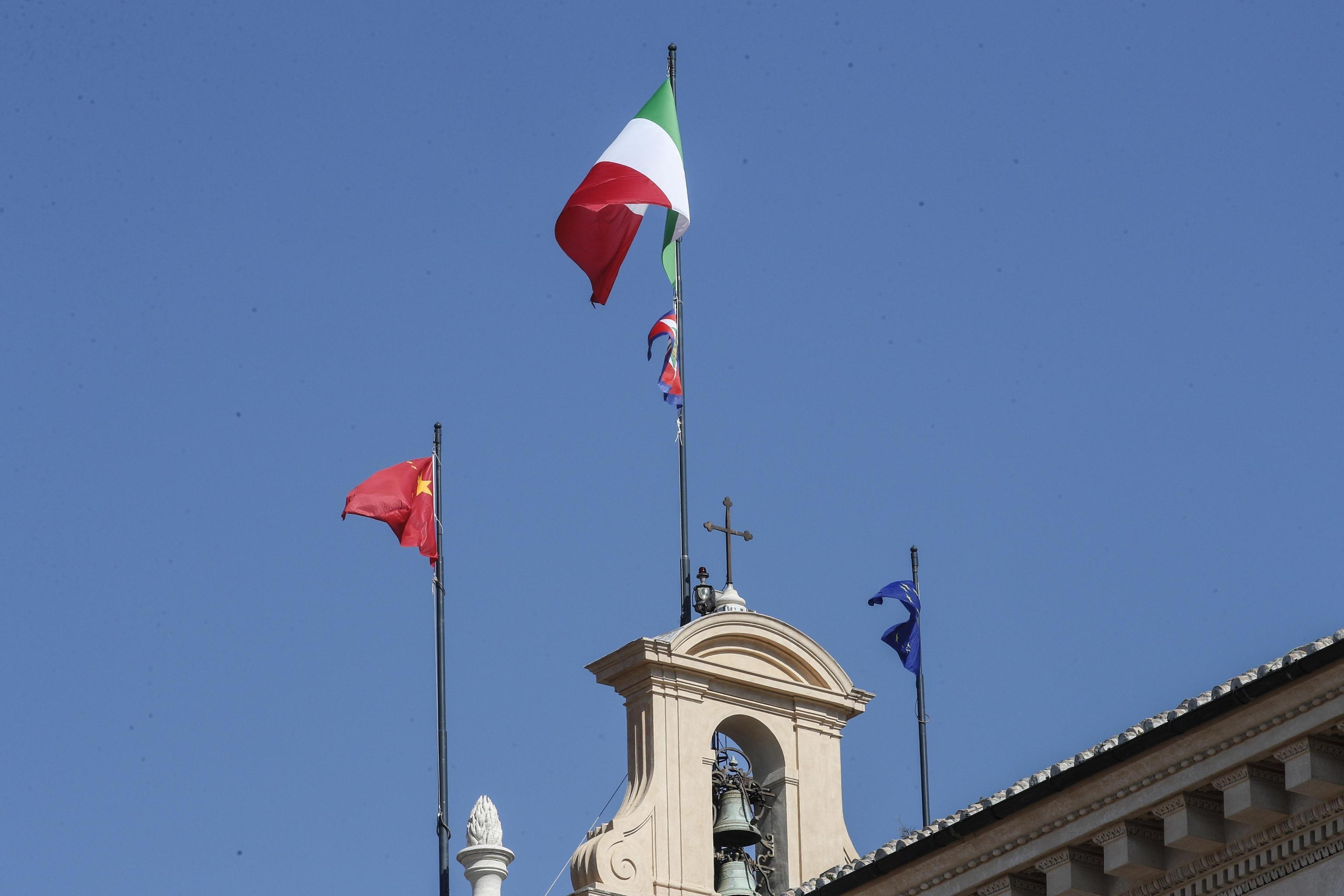 Una bandiera della Repubblica Popolare Cinese sventola sopra il Quirinale insieme a una bandiera della Repubblica Italiana e a un'altra dell'Unione Europea in occasione della visita di Xi Jinping