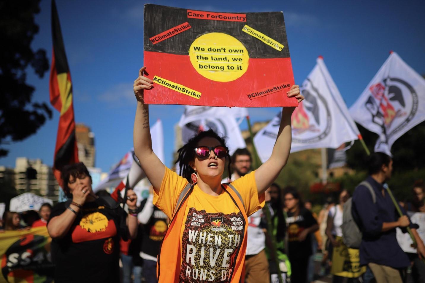 Una ragazza a Sidney mostra un cartello in cui si dice che ci vuole cura per il pianeta