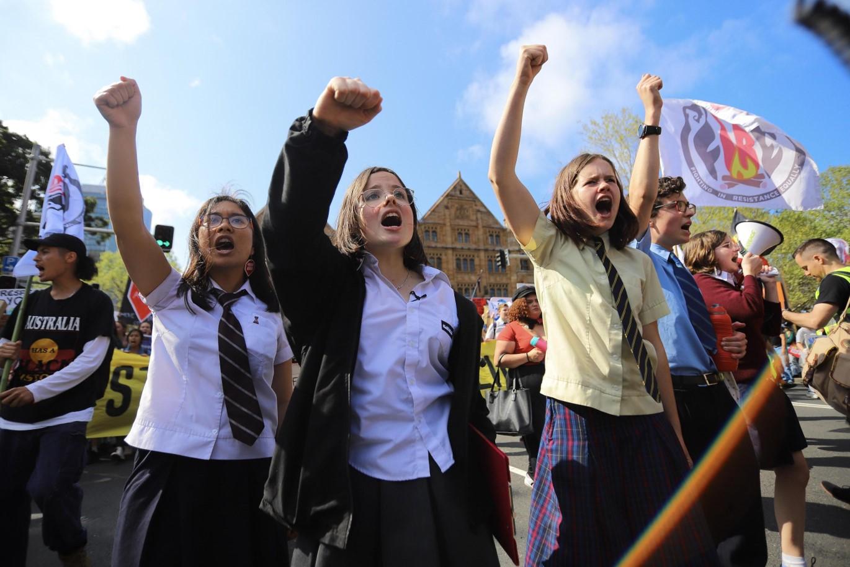Ragazzi e ragazze con i pugni chiusi in aria a Sidney contro il cambiamento climatico