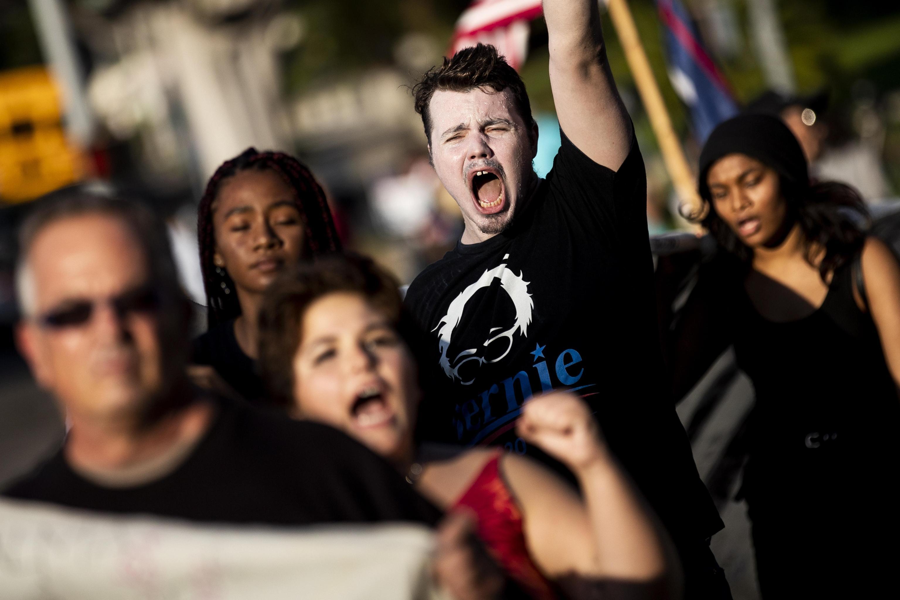 I manifestanti anti-Trump gridano mentre aspettano l'arrivo del presidente Donald Trump di fronte al Beverly Hills Hotel di Los Angeles