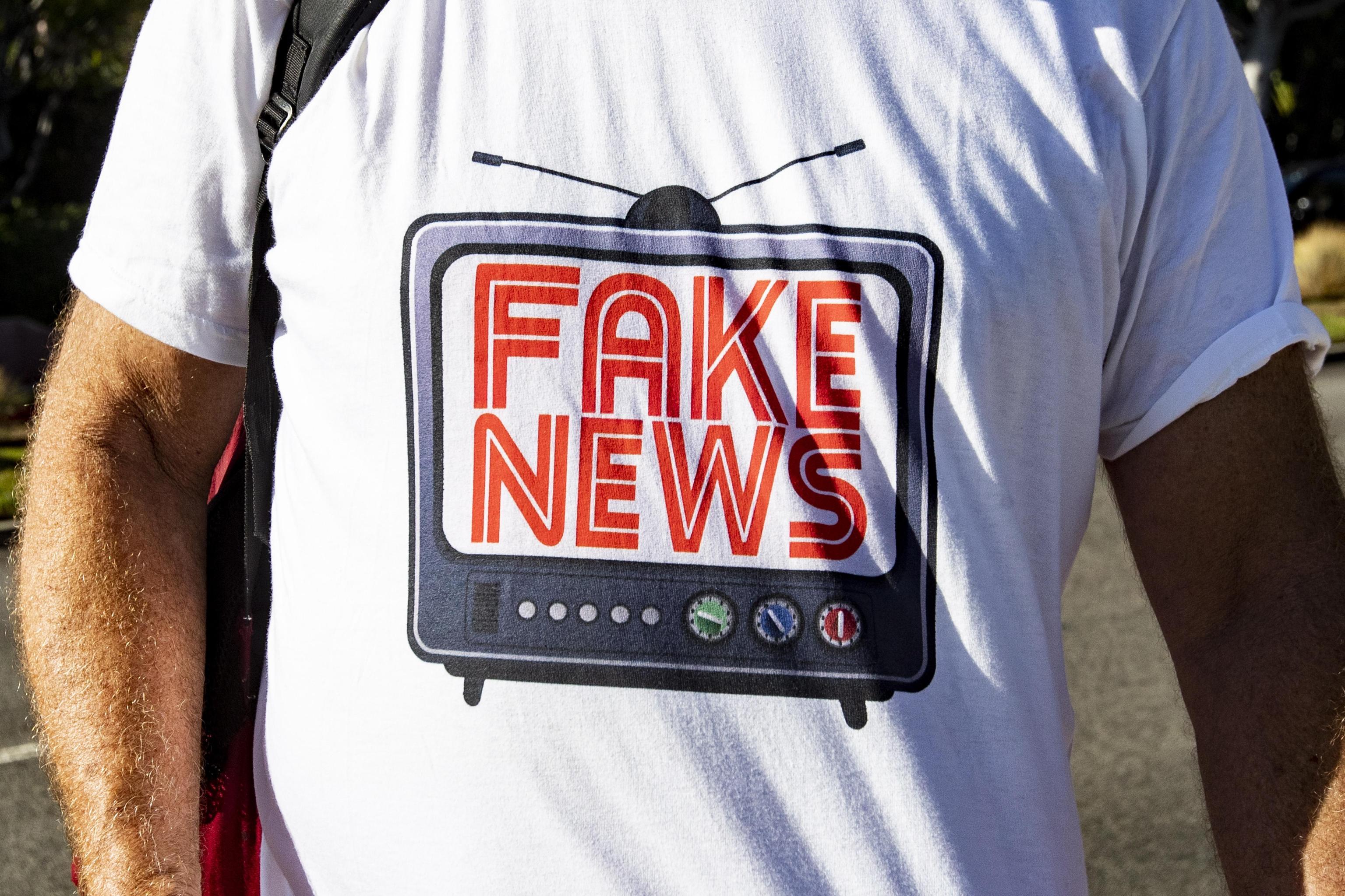 """Un oppositore indossa una maglietta che fa un chiaro riferimento all'accusa spesso rivolta al presidente Trump, quella di diffondere """"Fake News"""""""