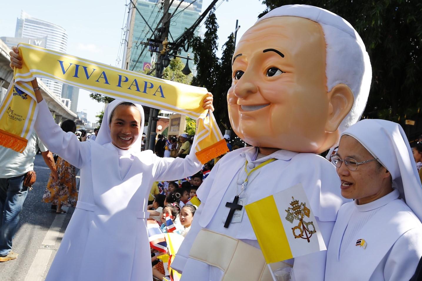 Un thailandese vestito con un costume di Papa Francesco sfila con delle suore con in mano una sciarpa che lo saluta
