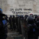 """La polizia in marcia verso la manifestazione. Sullo sfondo la scritta:""""I gilet gialli trionferanno"""""""