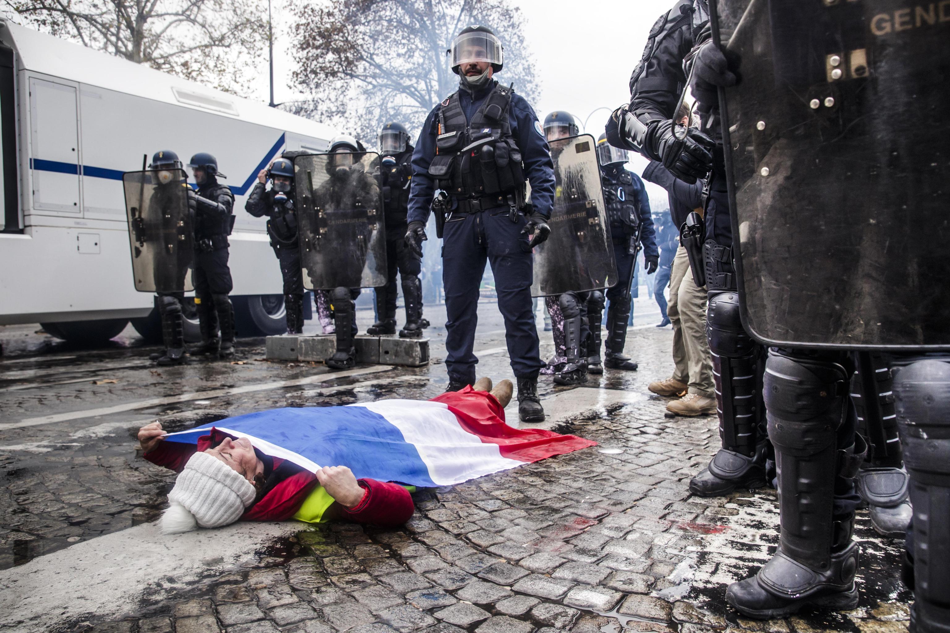 Una manifestante stesa a terra di fronte alla polizia il 24 novembre 2018